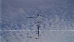 TV Television aerial antenna majestic cirrocumulus clouds. VHS tv tape effect of majestic cirrocumulus clouds on a summer afternoon with TV Television aerial stock footage