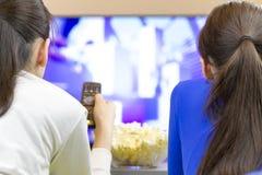 Två tonåringflickor som ner lägger, och hållande ögonen på tv Arkivbild