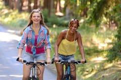 Två tonårs- flickor som rider deras cyklar Arkivfoto