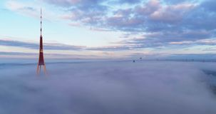 TV tower clouds flight above clouds. TV tower clouds drone up flight in Riga city with clouds stock footage