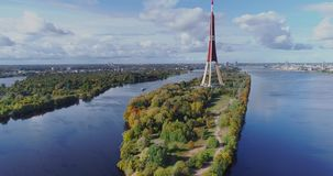 TV tower Riga city Drone flight, Zakusala island, Dugava river clouds. Riga TV tower, Daugava river Drone flight, passenger ship voyage, clouds in Latvia nature stock video