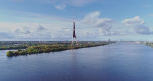 TV tower Riga city Drone flight, Zakusala island, Dugava river clouds. Riga TV tower, Daugava river Drone flight, passenger ship voyage, clouds in Latvia nature stock footage