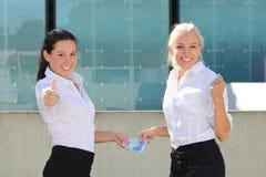 Två tummar för affärskvinnor upp med eurosedlar Arkivfoto