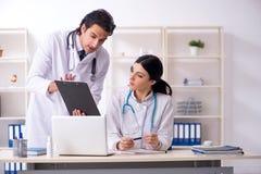Tv? unga doktorer som arbetar i kliniken royaltyfri bild