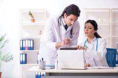 Tv? unga doktorer som arbetar i kliniken arkivbild