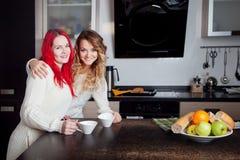 Två unga flickor i köket som talar och äter Arkivfoto