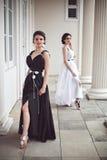 Två unga flickor i svartvita långa klänningar Royaltyfri Bild