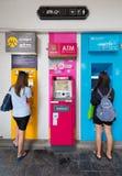 Två unga flickor på ATM i Thailand Royaltyfri Fotografi