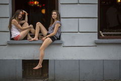 Två unga flickor som sitter på fönsterbrädan som nattklubben på aftonen tajmar Royaltyfri Bild