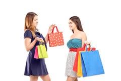 Två unga kvinnlig, når de har shoppat att posera med shopping, hänger lös Arkivbild