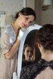 Tv? unga kvinnor i tappningkl?nningar ser de till och med en spegel, en reflexion av f?r?lskelse Tillfogade ett litet korn, efter arkivfoto