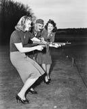 Två unga kvinnor och en soldat som ut försöker en maskingevär (alla visade personer inte är längre uppehälle, och inget gods finn Royaltyfri Fotografi