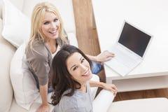Två unga kvinnor som använder sofaen för bärbar datordatorutgångspunkt Arkivfoto