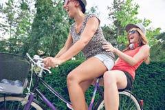 Två unga kvinnor som har på cykeln Arkivfoton