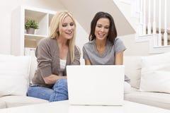 Två unga kvinnor som hemma använder bärbar datordatoren Royaltyfri Foto