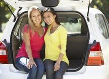 Två unga kvinnor som sitter i stam av bilen Arkivfoton
