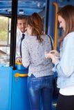 Två unga kvinnor som stiger ombord bussen och köper biljetten Fotografering för Bildbyråer