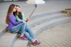 Två unga kvinnor som tar bilder med din smartphone Arkivfoton