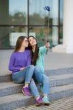 Två unga kvinnor som tar bilder med din smartphone Royaltyfri Fotografi