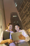Två unga le affärskvinnor som utomhus ser den digitala tabellen på natten Royaltyfri Bild