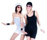 Två unga nätt kvinnor som poserar med solglasögon Arkivfoto