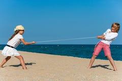 Två ungar som har en dragkamp på stranden. Arkivfoton