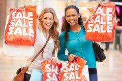 Två upphetsade kvinnliga shoppare med Sale påsar i galleria Royaltyfri Bild