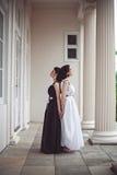 Två ursnygga flickor i svartvita långa klänningar Royaltyfri Bild