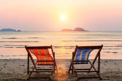 Två vardagsrumstolar på solnedgångstranden relax Arkivfoton
