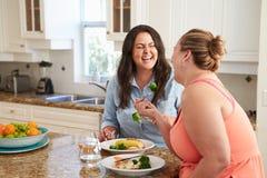 Två överviktiga kvinnor bantar på äta sunt mål i kök Arkivbild