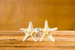 Två vigselringar med sjöstjärna två på trätabellen Arkivfoton