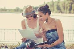 Två vänkvinnor som studerar och ser utomhus lyckliga Arkivfoto