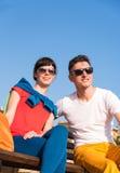 Två vänner som kopplar av på bänken efter en promenad Fotografering för Bildbyråer
