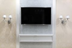 TV on the wall with a decor and two sconces on the sides stock photos