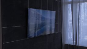 TV on the wall, turning channels. Slow motion with crane stock video