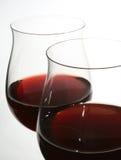 Två wineexponeringsglas med rött vin Arkivbilder