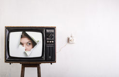 TV and woman looking out of it. Royalty Free Stock Photo