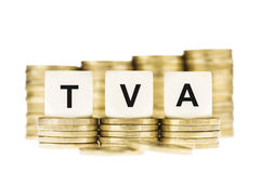 TVA (налог на добавленную стоимость) на кучах золотых монеток с белым Backgr Стоковые Фотографии RF