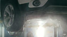 Tvagningen lyxiga SUV under botten i såplöddret vid vatten vattnar med slang - under botten, slut upp lager videofilmer