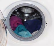 Tvagningmaskin med den öppna dörren och färgrik linne inom royaltyfri foto