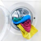 Tvagningmaskin som laddas med färgrik kläder royaltyfria bilder