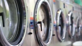 Tvagningmaskiner på tvätterit tvättar kulöra kläder och täcker