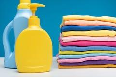 Tvagningtvättmedel och hög av rena plagg på tabellen Royaltyfria Bilder