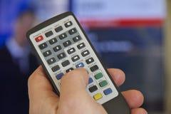 TVfjärrkontroll och hand Arkivbild