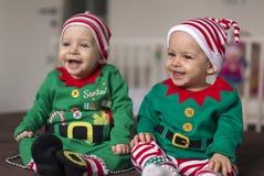 Tvilling- behandla som ett barn älvahjälpredan av jultomten Arkivbild