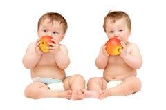 Tvilling- behandla som ett barn flickor äter royaltyfri bild