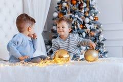 Tvilling- bröder framme av julträdet med stearinljus och gåvor förälskelse, lycka och stort familjbegrepp royaltyfri fotografi