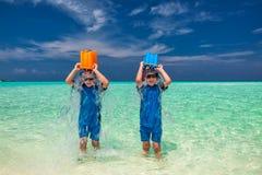 Tvilling- bröder på tropiska ferier som har roligt hällande vatten över Royaltyfri Foto