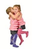 Tvilling- flickor firar Isolerat på vit Lyckliga barn Royaltyfri Bild