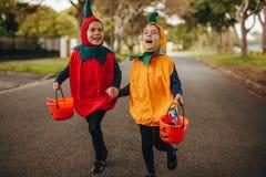 Tvilling- flickor i halloween kostymerar ut vägen royaltyfria bilder
